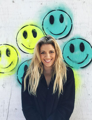 jessica clark in front of smiley face graffiti