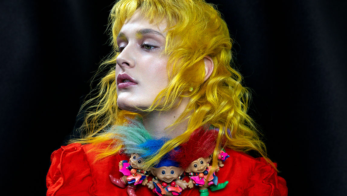 model with yellow hair colour wearing troll necklace