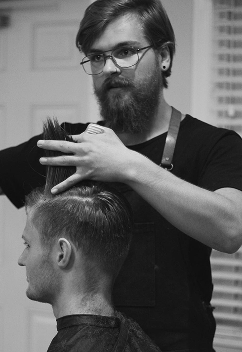 barber Cody Dunbar working on a client's hair at Bourbon Barbershop in Saskatchewan