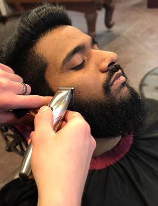 cody dunbar blanche macdonald graduate shaving a client's beard