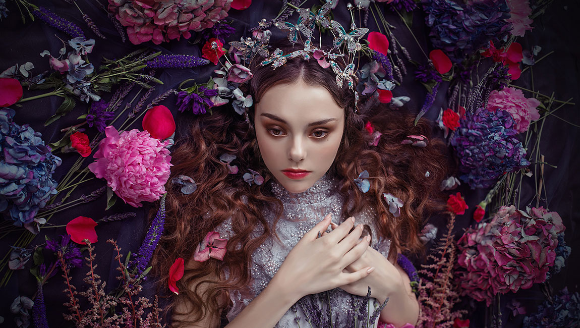 elfin model surrounded by flowers with beautiful makeup applied