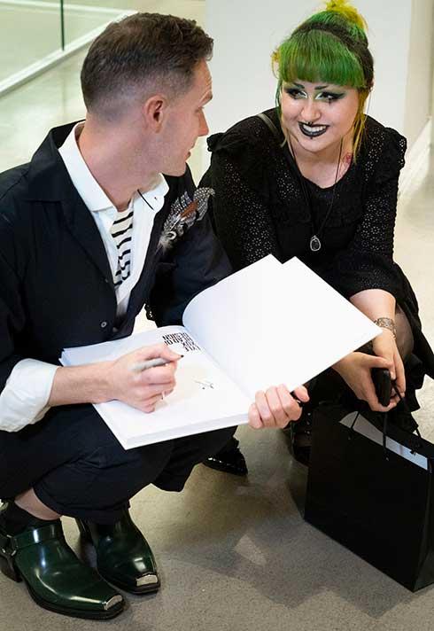 Lyle Reimer autographs his new book Head of Design for an aspiring artist