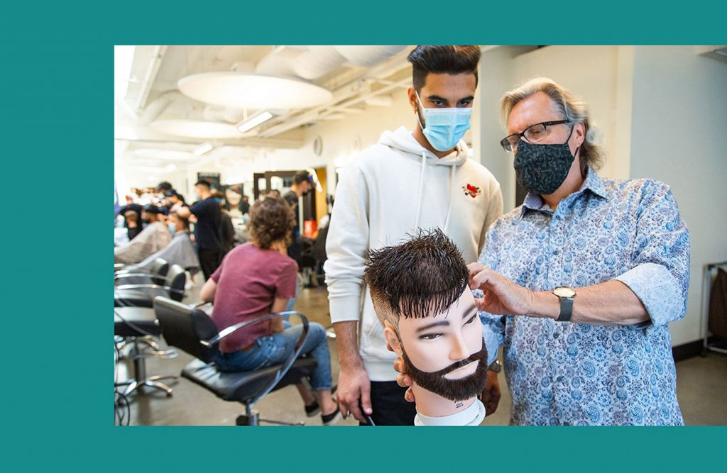 student with instructor hands on barbering school